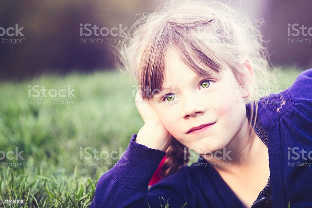 Six Year Old Girl Daydreaming Outdoors Laying In Grass stock photo