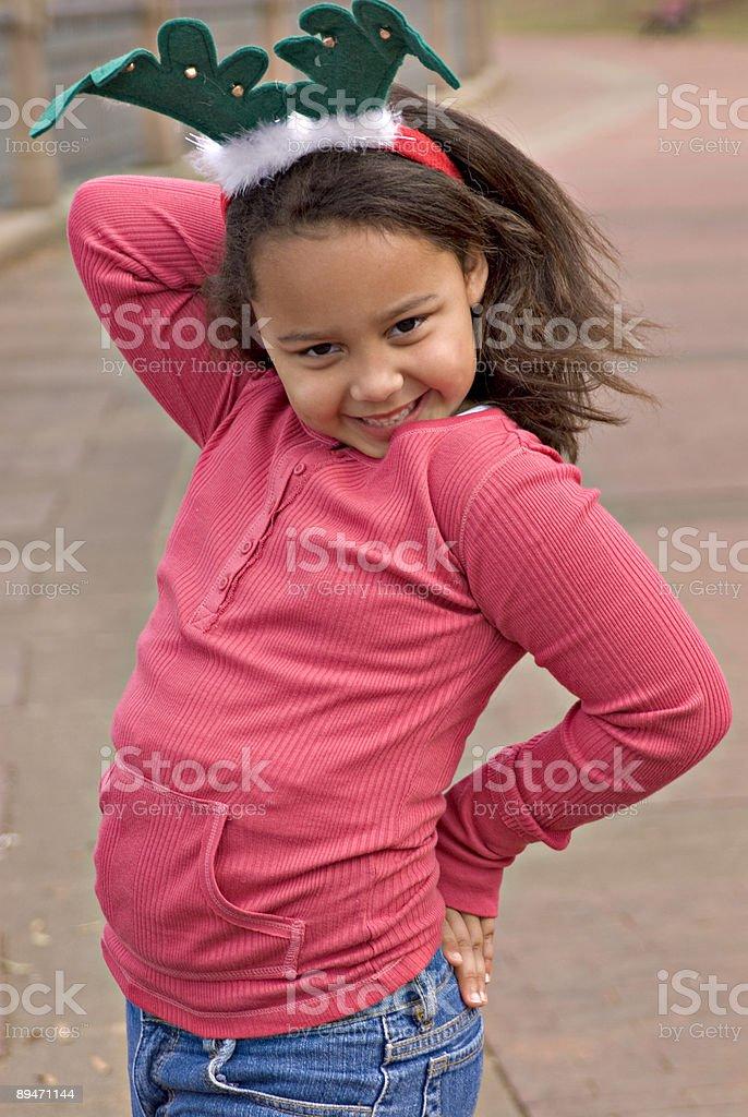 Sechs Jahre alter Lächeln Mädchen trägt eine Santas Rentier-Mütze Lizenzfreies stock-foto