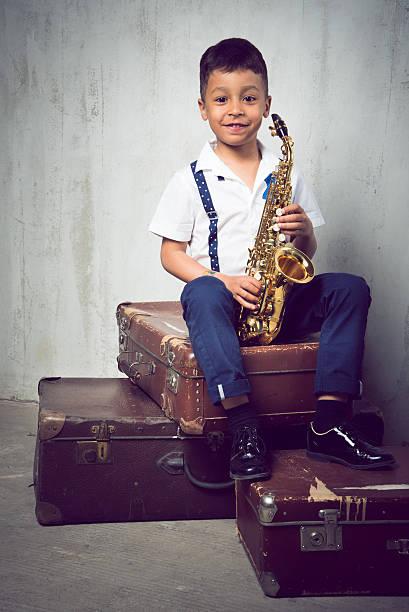sechs jahre alter junge mit saxophon sitzen auf retro-koffer - lautbildungsspiele stock-fotos und bilder