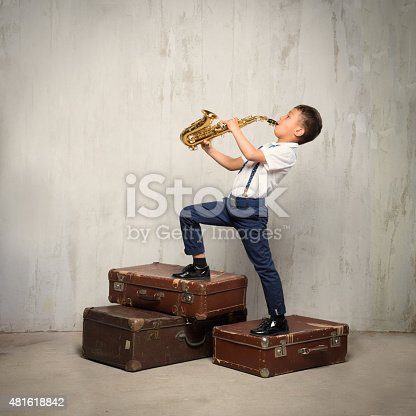 six years old boy stand on retro suitcases and play sax. instagram toned