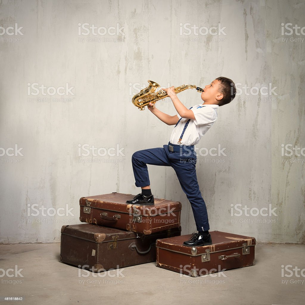six years old boy stand on suitcases and play sax stock photo