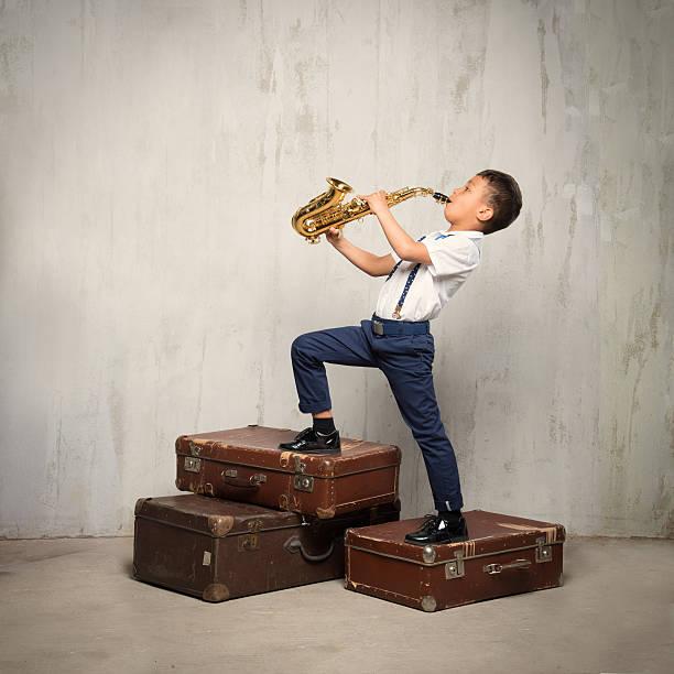 sechs jahre alter junge stand auf koffer und spielen sax - lautbildungsspiele stock-fotos und bilder
