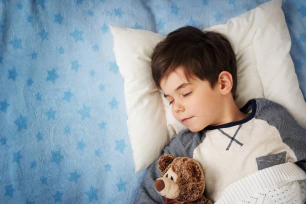 sechs jahre alte kind schläft im bett mit radiowecker - bett für jungs stock-fotos und bilder