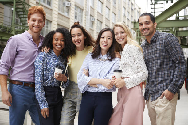 six young adult coworkers standing outdoors, group portrait - millennial generation stock photos and pictures