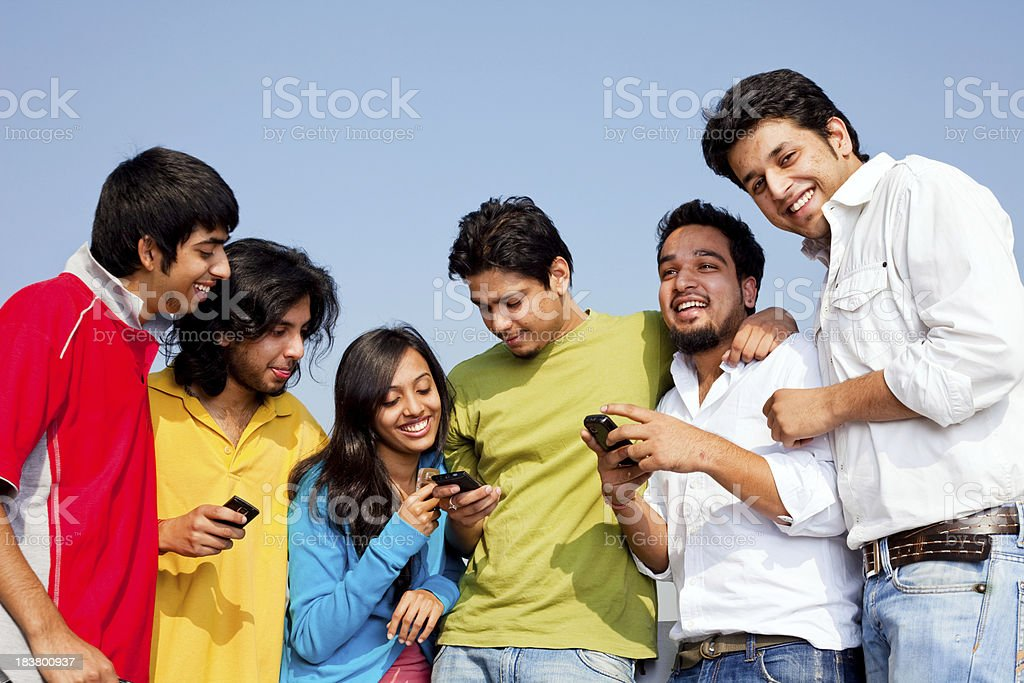 Six Young Indian Friends People reading SMS on cell phones royalty-free stock photo