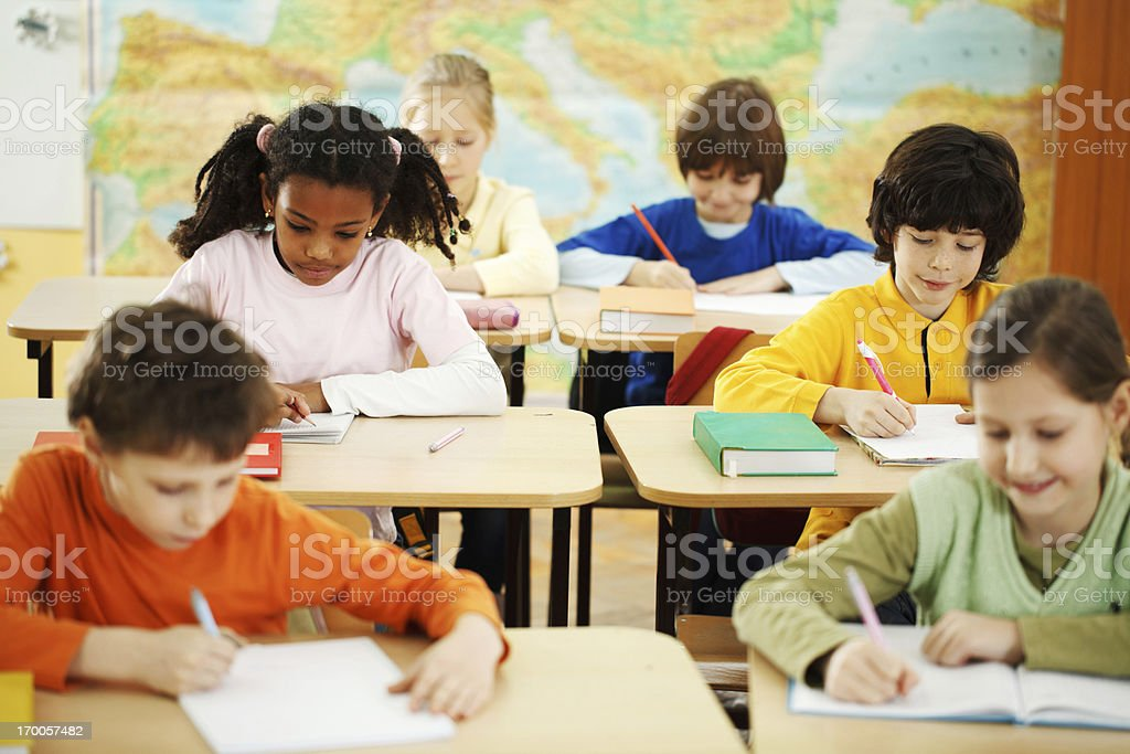 Six young pupils writing on notebooks in classroom royalty-free stock photo