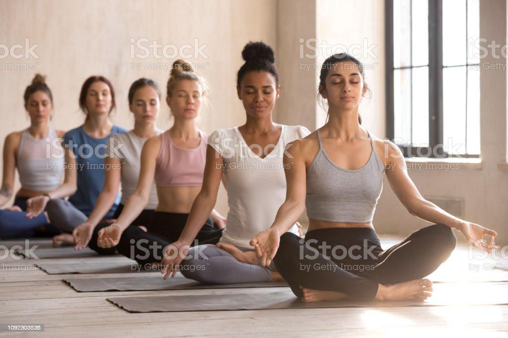 Zes jonge vrouwen mediteren in lotus houding zitten - Royalty-free Ademhalingsoefening Stockfoto