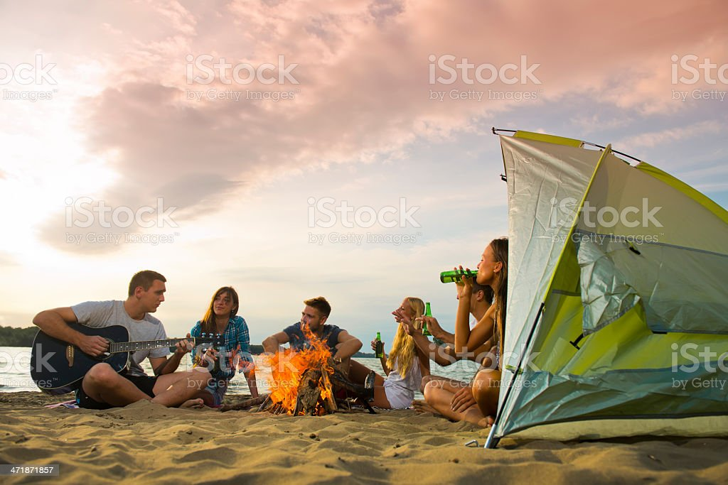 Six youngsters camping on beach, making music  stock photo
