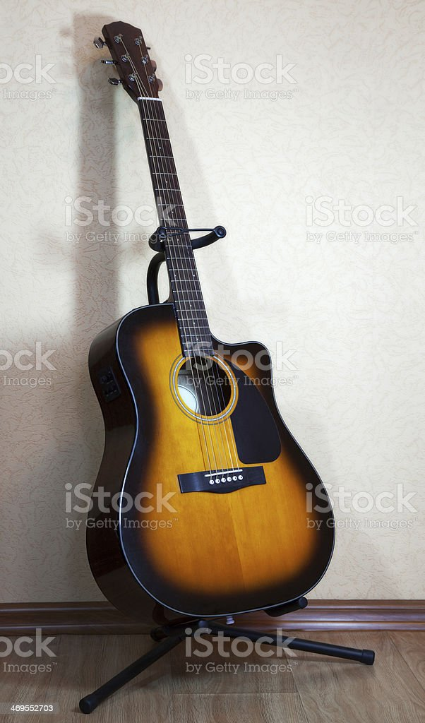 six-string acoustic guitar on a stand royalty-free stock photo