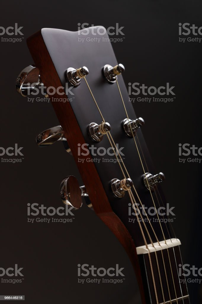 Six-stringed acoustic guitar head with tuning pegs close-up stock photo