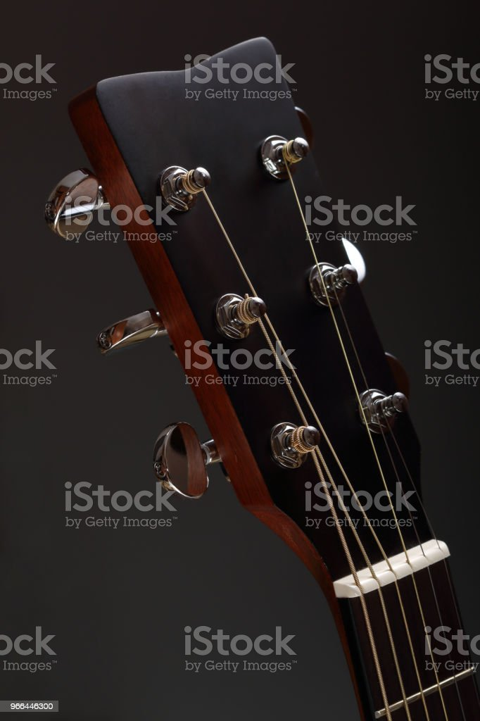 Six-stringed wooden acoustic guitar head with tuning pegs stock photo