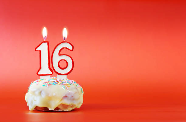 sixteen years birthday. cupcake with white burning candle in the form of number 16. vivid red background with copy space - number 16 stock photos and pictures