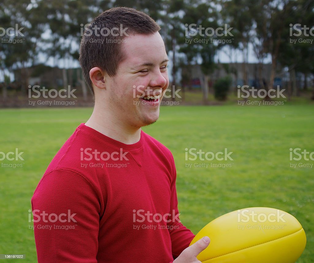 Sixteen-year-old boy smiling while holding football at park stock photo