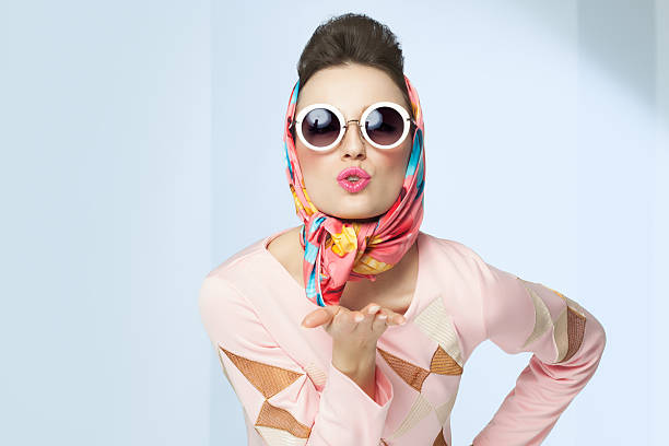 Sixties Style Girl Sixties style girl blowing a kiss. Retro fashion with silk scarf and sunglasses. headscarf stock pictures, royalty-free photos & images