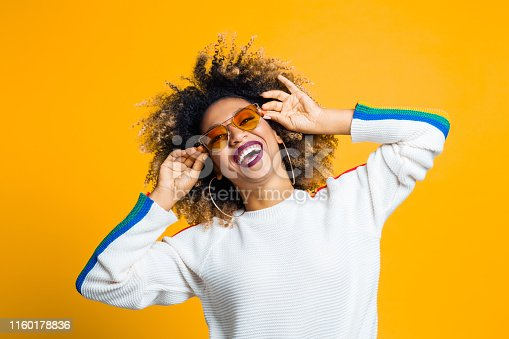 Portrait of stylish afro young woman with sunglasses laughing against yellow background