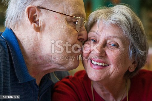After sixty years together, senior octogenarian couple who is still in love. Man is kissing the woman on the cheek, which makes her smile.