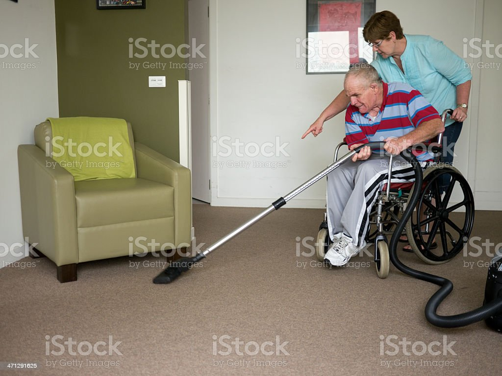 Sixty-six year old man vacuuming stock photo