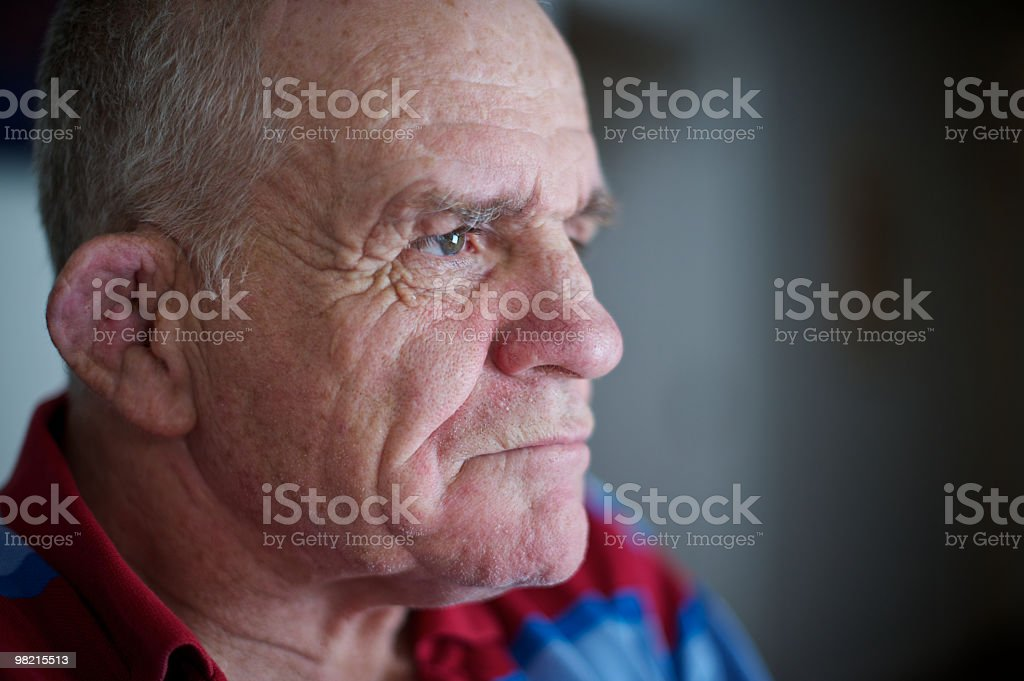 Sixty-six year old man with a disability looking out window royalty-free stock photo