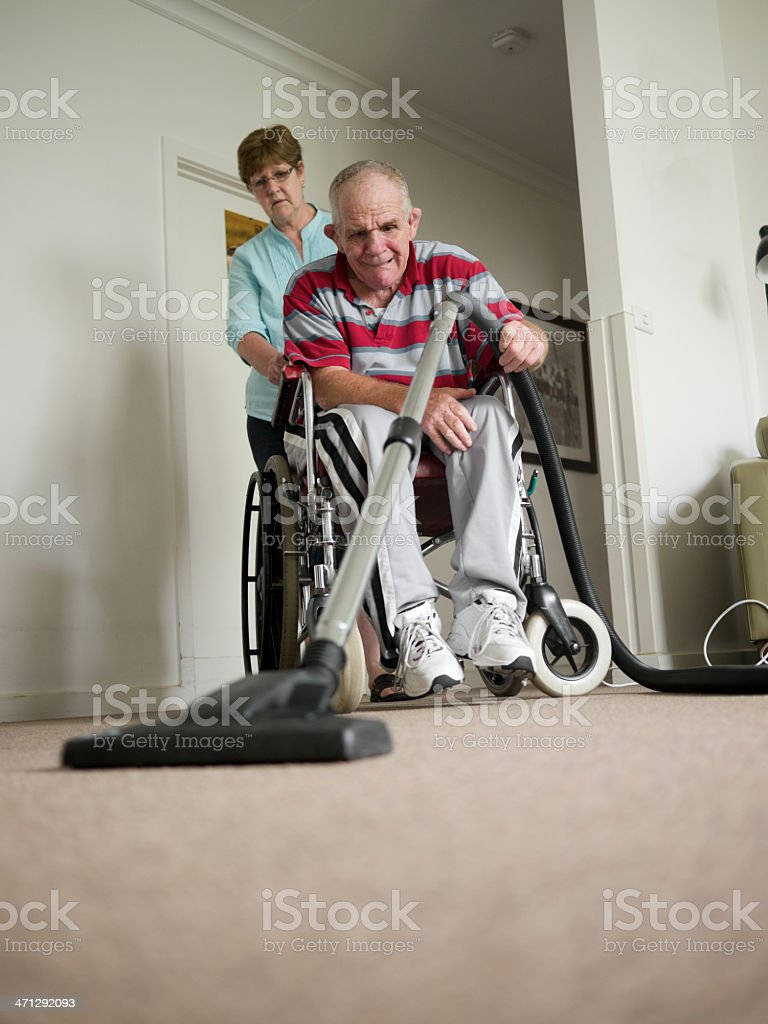 Sixty-six year old man with a disability vacuuming stock photo