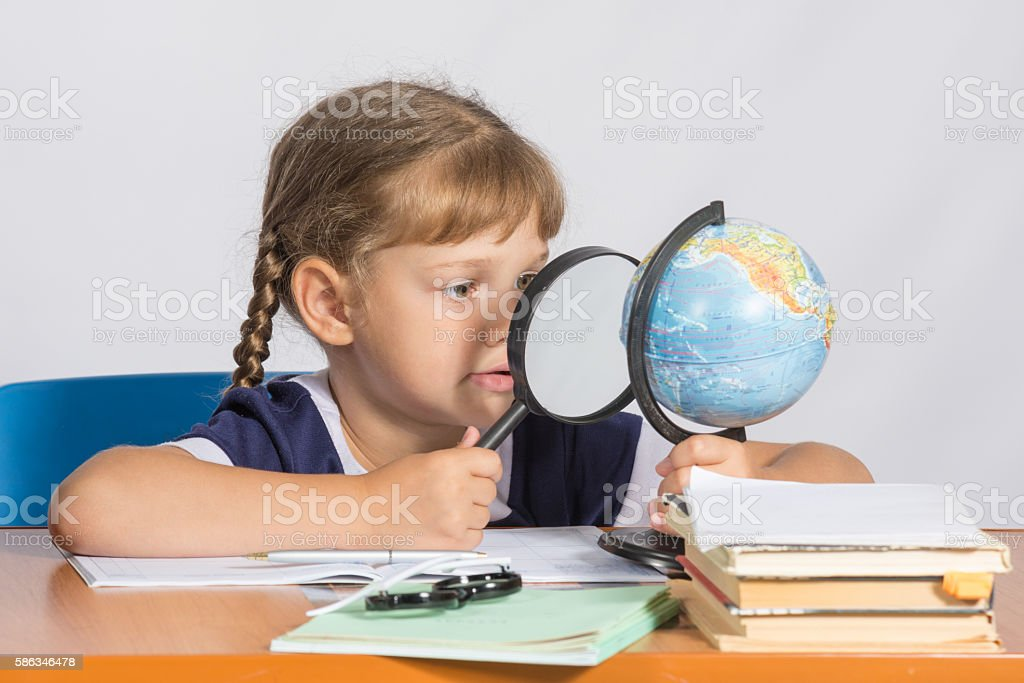 Six-year girl sitting at table and looks at globe through stock photo