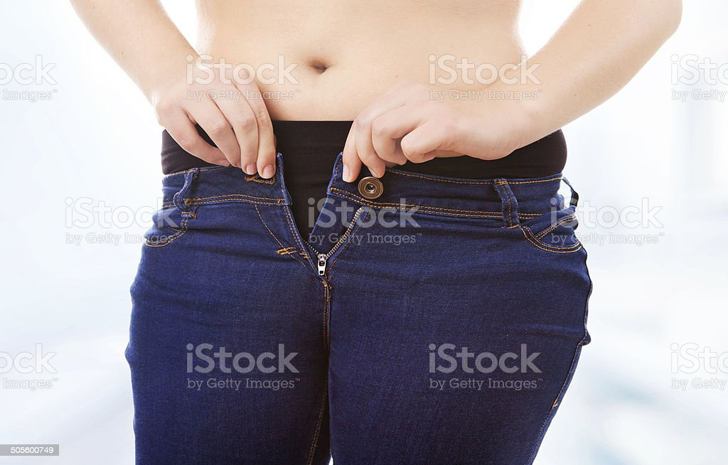 Size 40 woman zipping tight jeans stock photo