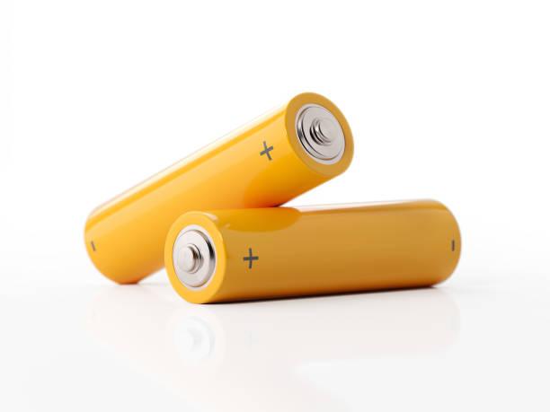 zwei gelbe batterien der größe aa auf weißem hintergrund - batterie stock-fotos und bilder