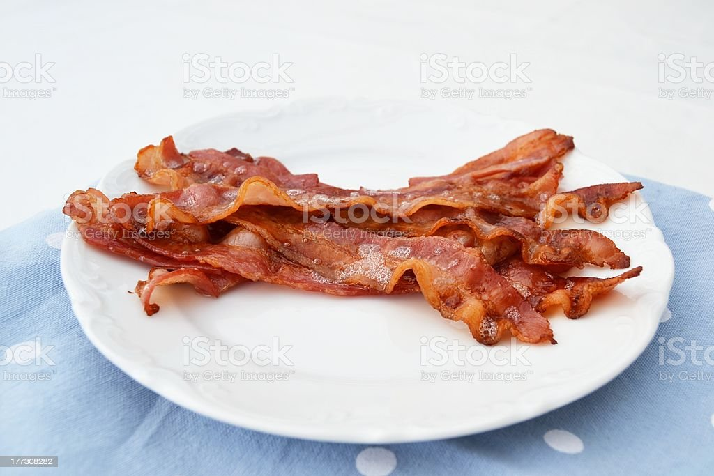 Sizzling hot bacon strips on a dinner plate on tablecloth stock photo