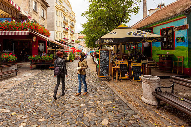 Skadarlija Street in Belgrade, Serbia Belgrade, Serbia - July 3, 2014: Women talking in the middle of the street in Skadarlija, a bohemian district, in Belgrade, Serbia. Various restaurants can be seen in the background. belgrade serbia stock pictures, royalty-free photos & images