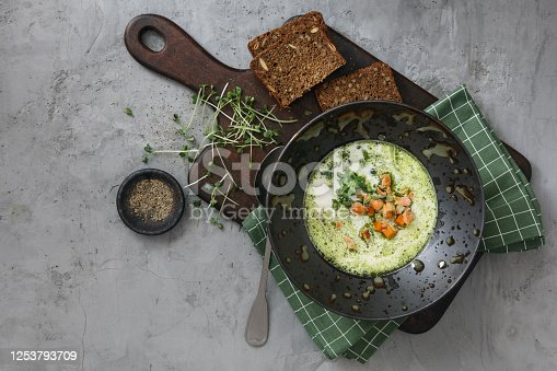 Skagen Fish Soup Green Herb Oil. Tradition Danish Soup. Flat lay top-down composition on concrete background. Horizontal image with copy space.