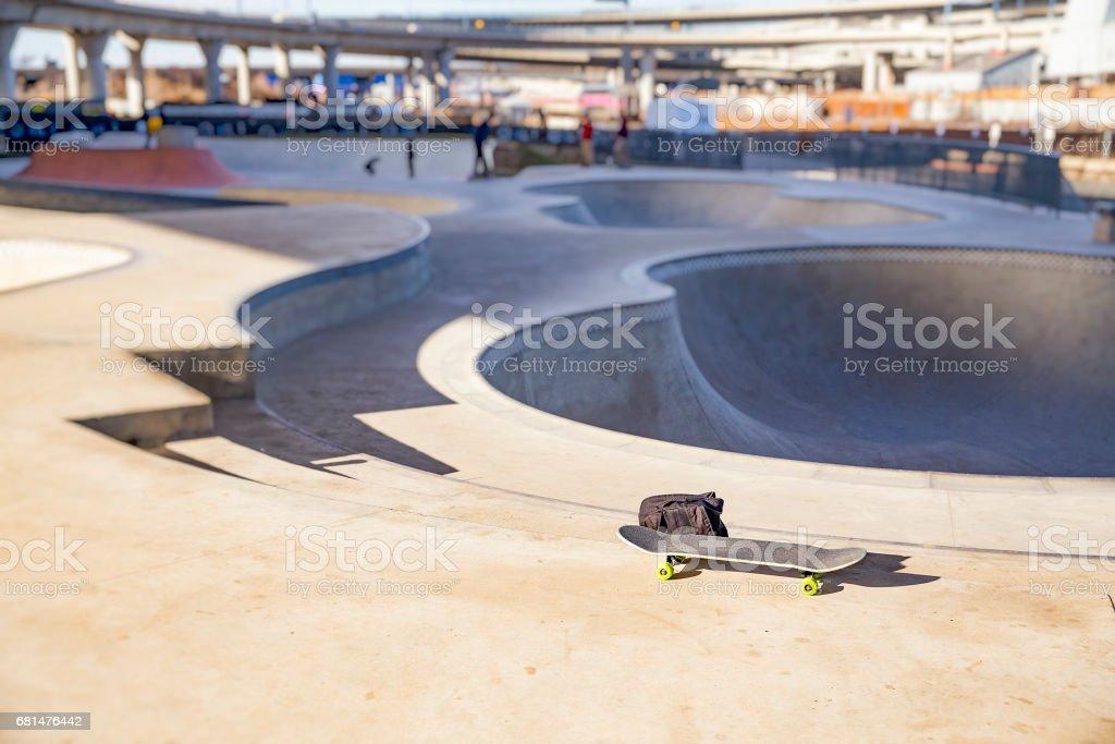 skateboard and backpack in skate park stock photo
