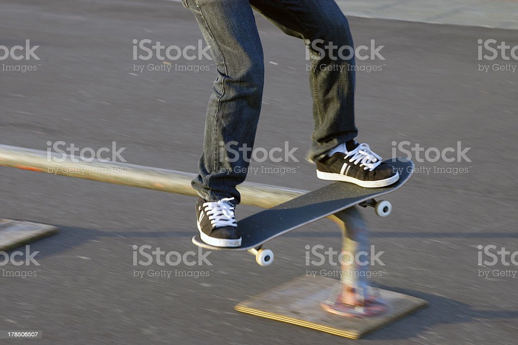 Skateboard and sneakers teenager rail slide stock photo