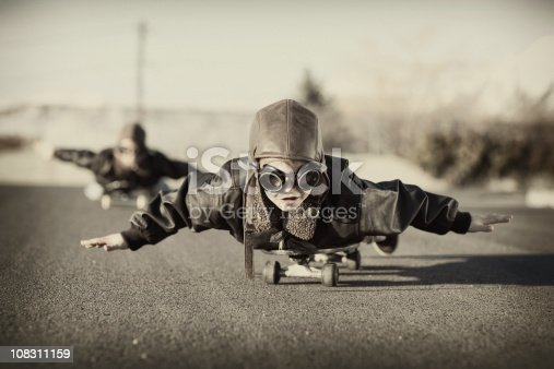 A couple of young boys love to fly, albeit down a hill on a skateboard.