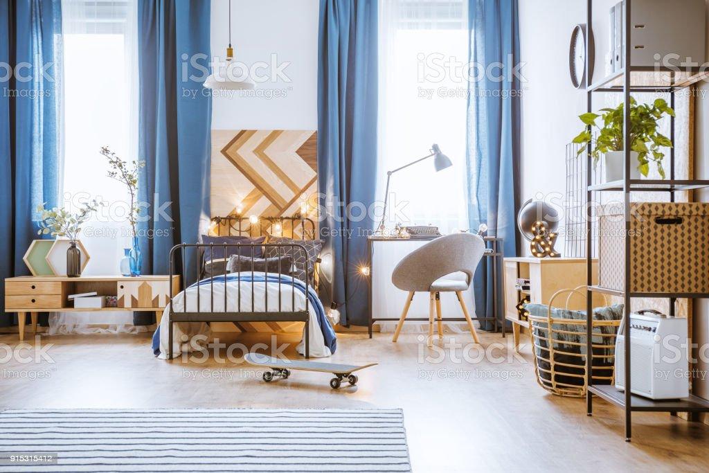 Skateboard in blue bedroom interior stock photo