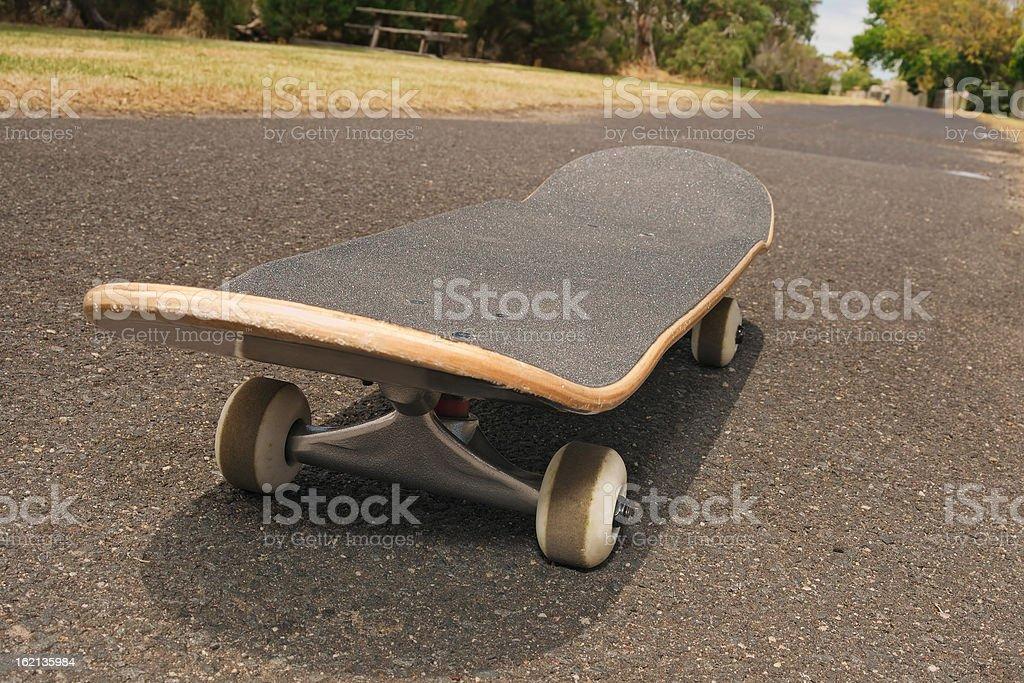Skateboard on asphalt footpath royalty-free stock photo