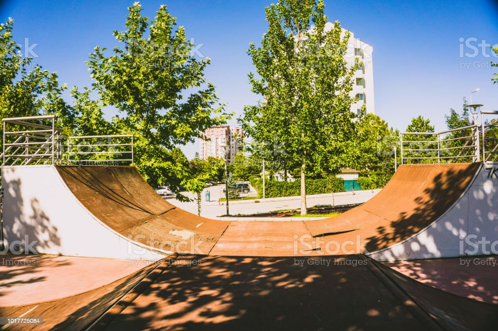 Skateboard park on a sunny day, trees at the background.