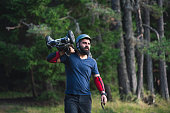 Skateboard rider holding his off road electric skateboard in nature, looking away