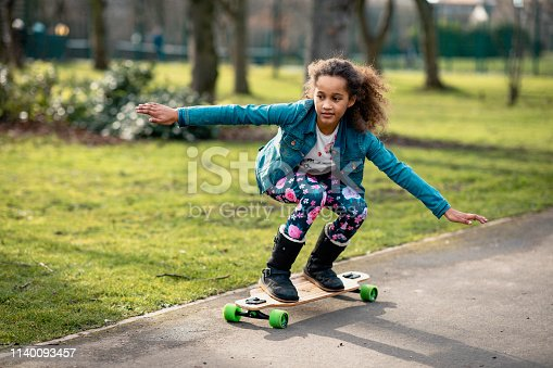 Girl skateboarding down a path in a public park.