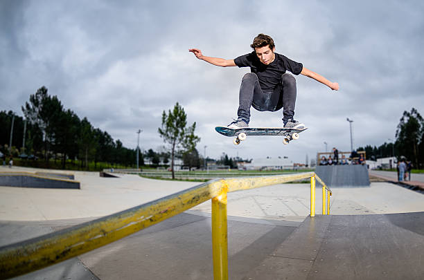 skateboarder doing a ollie - skateboarding stock pictures, royalty-free photos & images