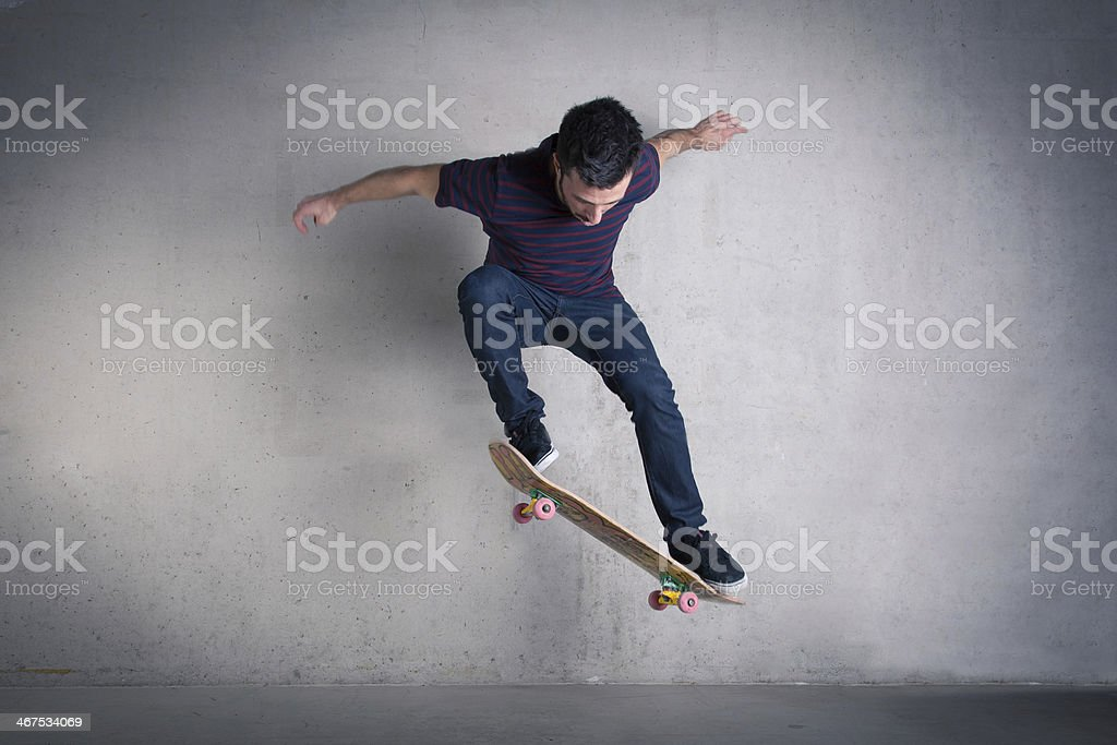 Skateboarder doing a skateboard trick ollie against concrete stock photo