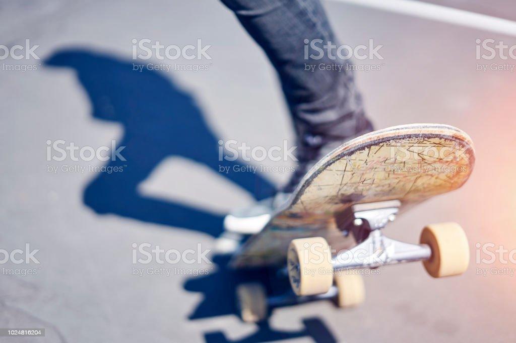 61ccb9f1 Skatista fazendo um truque em um parque de skate, skate velho close-up foto