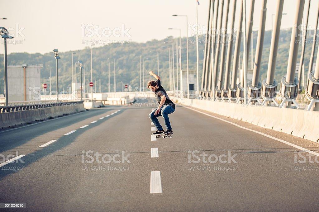 Skateboarder doing jumps on the city road bridge stock photo
