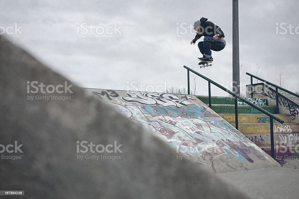 Skateboarder doing Ollie over the rail in a skatepark stock photo