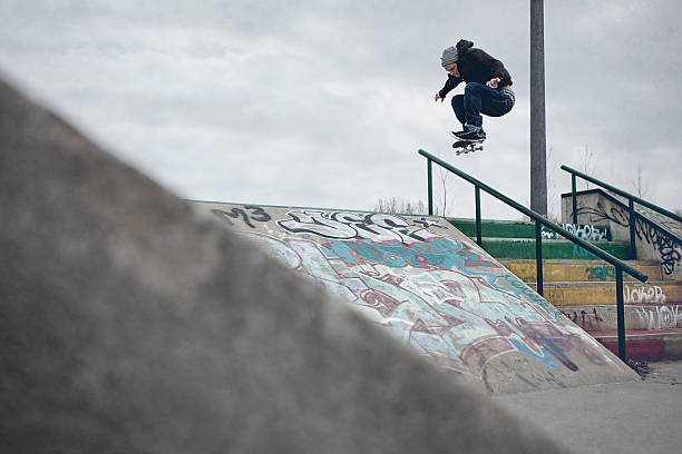 skateboarder doing ollie over the rail in a skatepark - skatepark bildbanksfoton och bilder