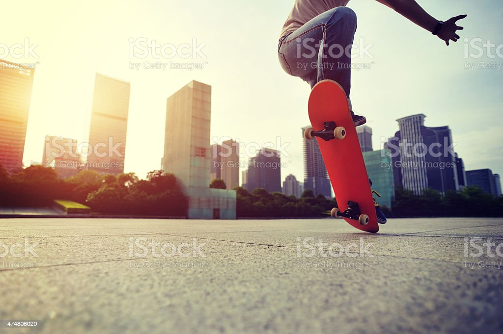 skateboarder doing skateboarding trick ollie on city stock photo