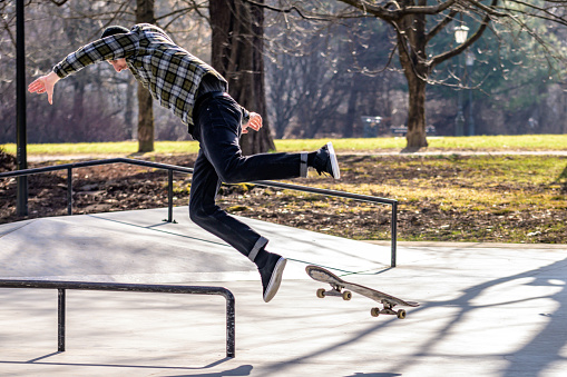 Man in mid-air while falling off his skateboard in a skatepark on a sunny day.