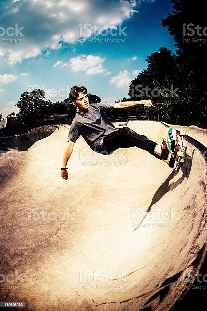 Skateboarder grinding in skatepark stock photo