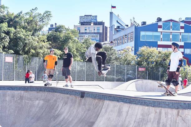 A skateboarder in a deep concrete bowl stock photo