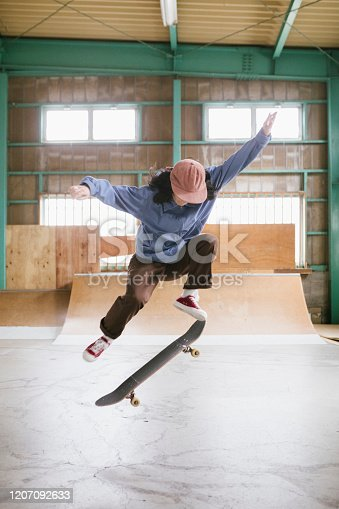 Young female skateboarder practicing her skills in a indoor skatepark in Tokyo.