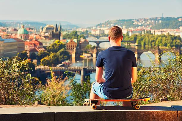 Skateboarder in the city Skateboarder is sitting on the skateboard and looking out over the city. Prague, Czech Republic. bohemia czech republic stock pictures, royalty-free photos & images