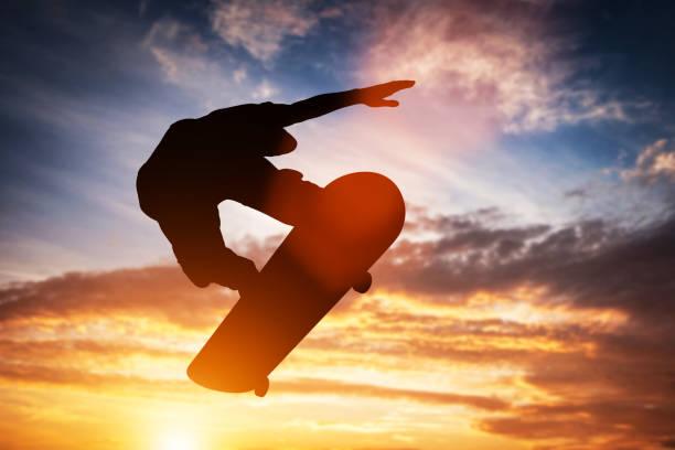 夕暮れ時のジャンプのスケートボーダー。 - スケートボード ストックフォトと画像